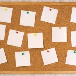white notes pinned to cork board
